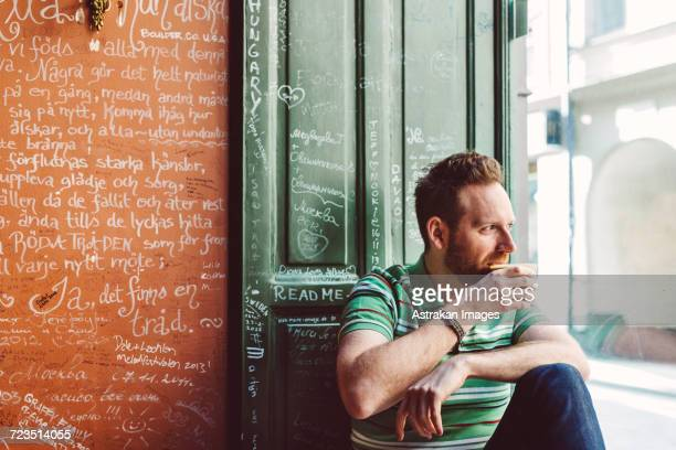 Sweden, Stockholm, Gamla Stan, Man holding coffee cup in cafe