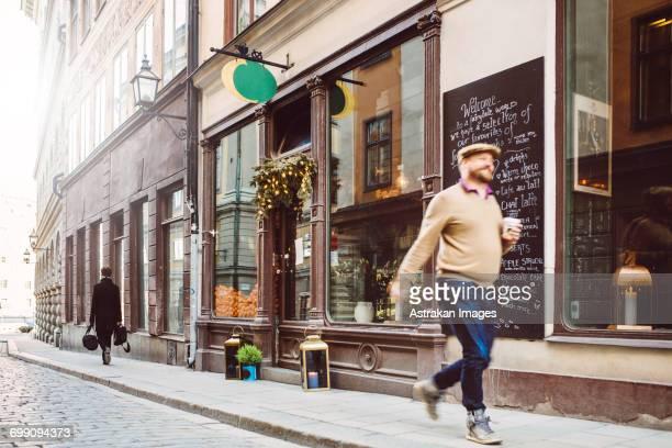 Sweden, Stockholm, Gamla Stan, Man walking by cafe