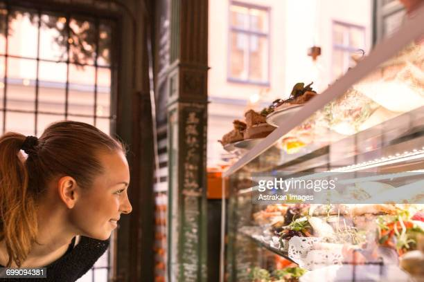 Sweden, Stockholm, Gamla Stan, Smiling woman looking at display in cafe