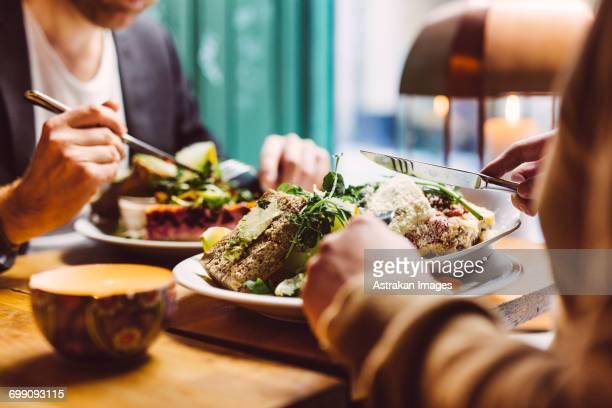 Sweden, Stockholm, Gamla Stan, Two men having lunch, close up of hands