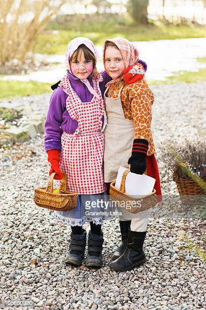 Sweden, Stockholm, portrait of two girls holding baskets, outdoors
