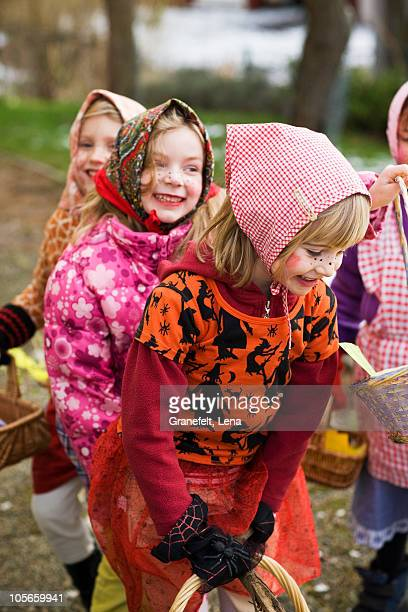 Sweden, Stockholm, three girls  in Easter costumes, outdoors