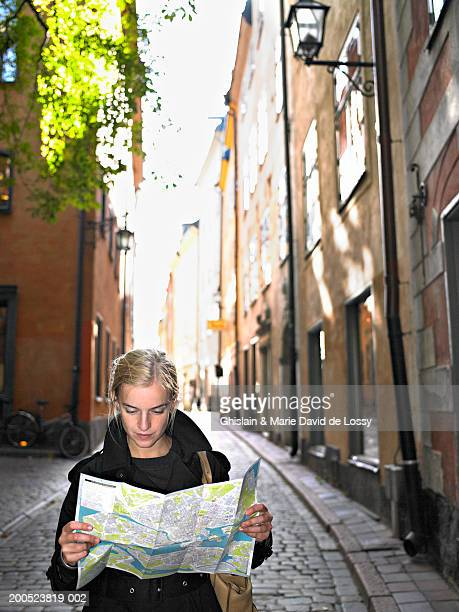 Sweden, Stockholm, woman reading map on street