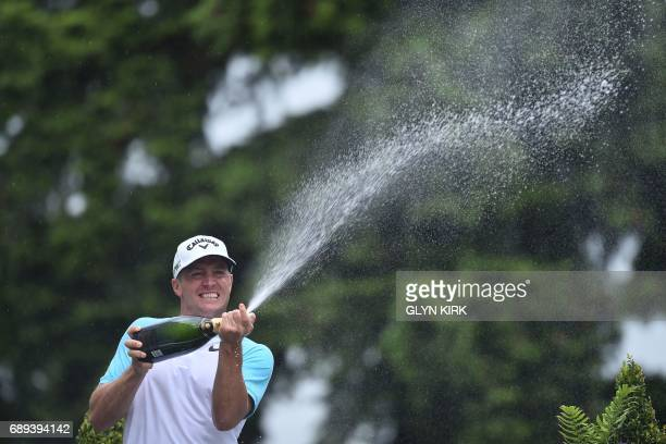 Sweden's Alex Noren sprays the champagne as he celebrates after winning the PGA Championship at Wentworth Golf Club in the town of Virginia Water in...