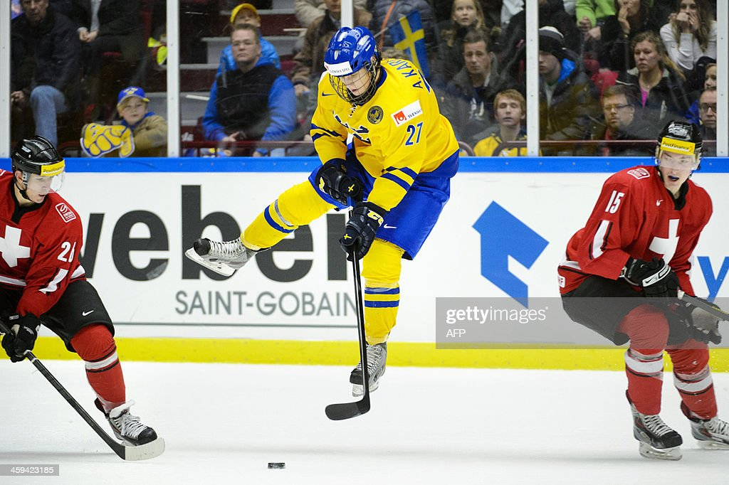 Sweden's Anton Karlsson (C) vies for the puck with Switzerland's Fabrice Herzog (R) and Marco Mueller (L) during the Group B preliminary round match Switzerland vs Sweden at the IIHF World Junior Ice Hockey Championships in Malmoe, Sweden on December 26, 2013.