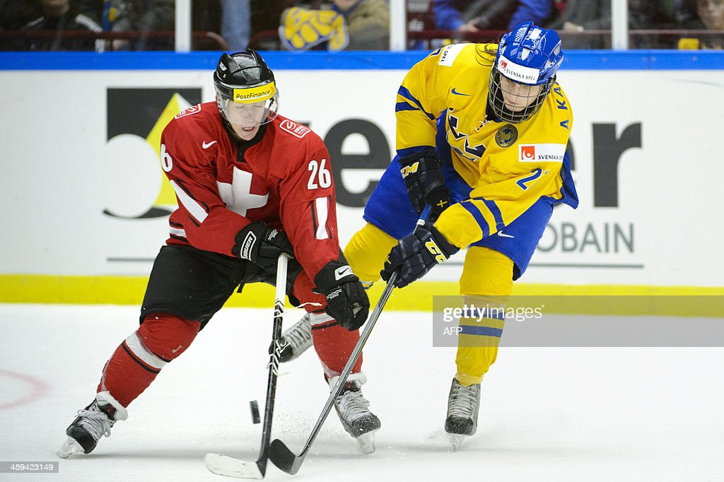 Sweden's Anton Karlsson (R) vies for the puck with Switzerland's Jason Fuchs (L) during the Group B preliminary round match Switzerland vs Sweden at the IIHF World Junior Ice Hockey Championships in Malmoe, Sweden on December 26, 2013.