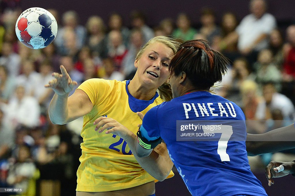 Sweden's centreback Isabelle Gullden (L) passes the ball as she vies with a french player during the women's preliminaries Group A handball match France vs Sweden for the London 2012 Olympics Games on August 1, 2012 at the Copper Box hall in London.