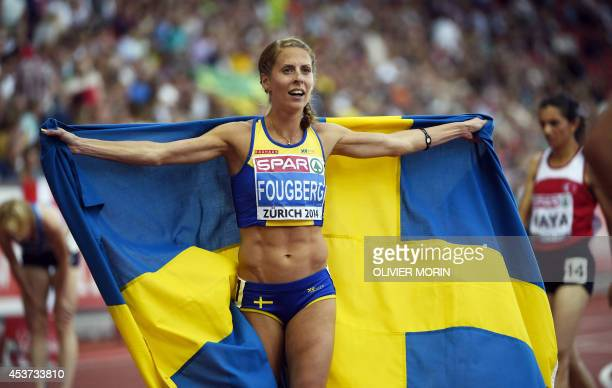 Sweden's Charlotta Fougberg holding her national flag celebrates after placing second in the Women's 3000m steeplechase final during the European...