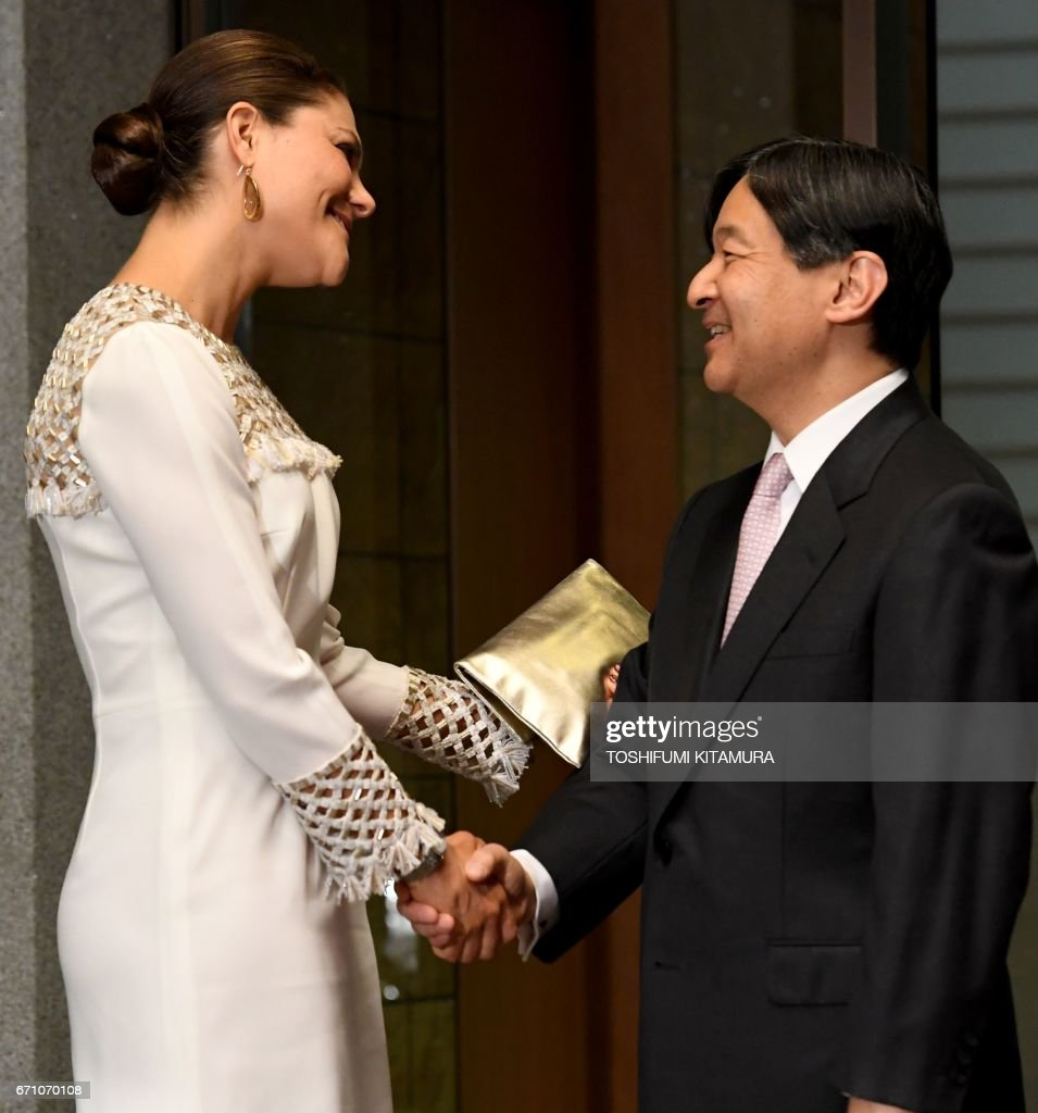 Swedens Crown Princess Victoria (L) is welcomed by Japanese Crown Prince Naruhito (R) upon her arrival at the entrance of Togu Palace to hold a banquet in Tokyo on April 21, 2017. / AFP PHOTO / Toshifumi KITAMURA