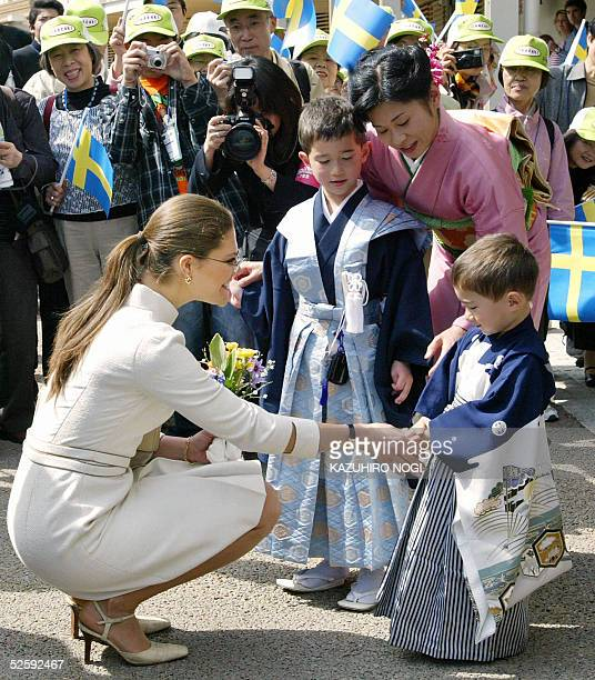 Sweden's Crown Princess Victoria shakes hands with kimono dressed Kevin Ahrlind who is living in local city Okazaki with his family as she arrives at...