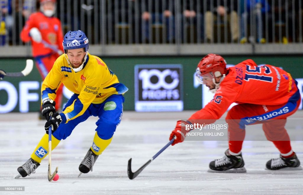Sweden's Daniel Andersson and Russia's Alan Dzhusoev (R) vie during Bandy World Championship final match Sweden vs Russia in Vanersborg, Sweden, February 3, 2013. AFP PHOTO / SCANPIX / ANDERS WIKLUND SWEDEN OUT