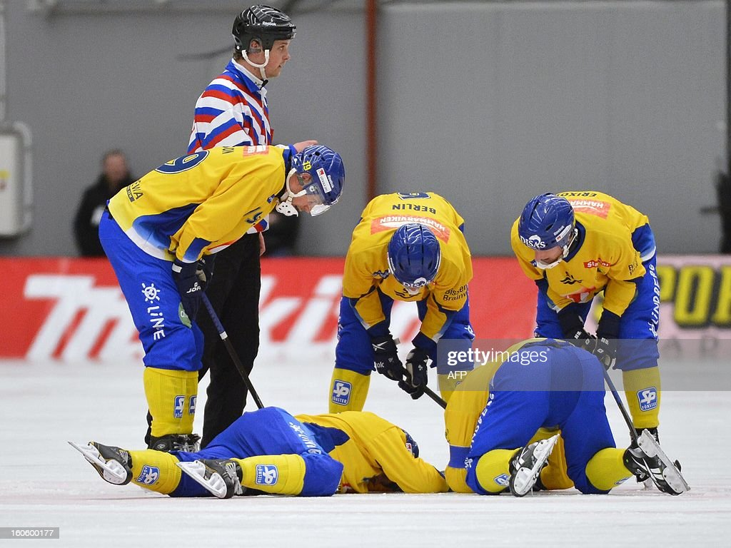 Sweden's Daniel Mossberg (laying down to the left) is injured after colliding with the referee during the Bandy World Championship final match Sweden vs Russia in Vanersborg, Sweden, February 3, 2013.