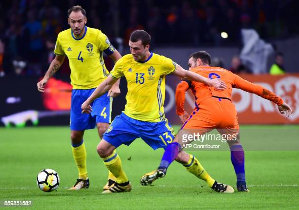 Sweden's defender Andreas Granqvist Sweden's midfielder Jakob Johansson and Netherlands' forward Vincent Janssen vie for the ball during the FIFA...