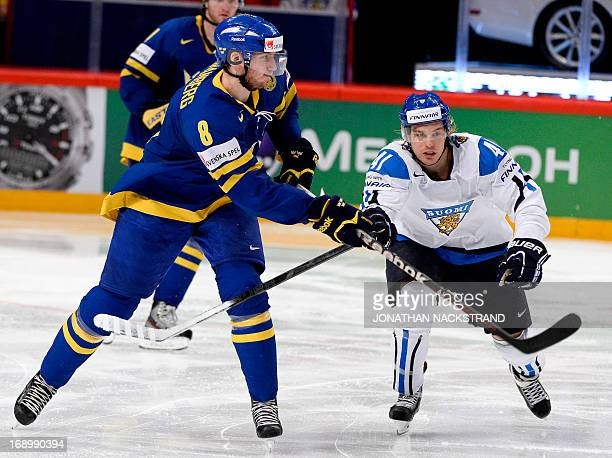Sweden's defender Petter Granberg and Finland's forward Antti Pihlstrom vie for the puck during the semifinal match Finland vs Sweden at the 2013...