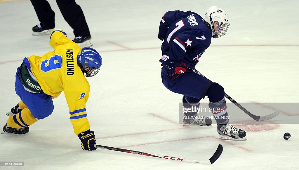 Sweden's defender Wilhelm Westlund (L) fights for the puck with US forward J T Compher during a quarter-final game of the IIHF U18 International Ice Hockey World Championship in Sochi on April 25, 2013.