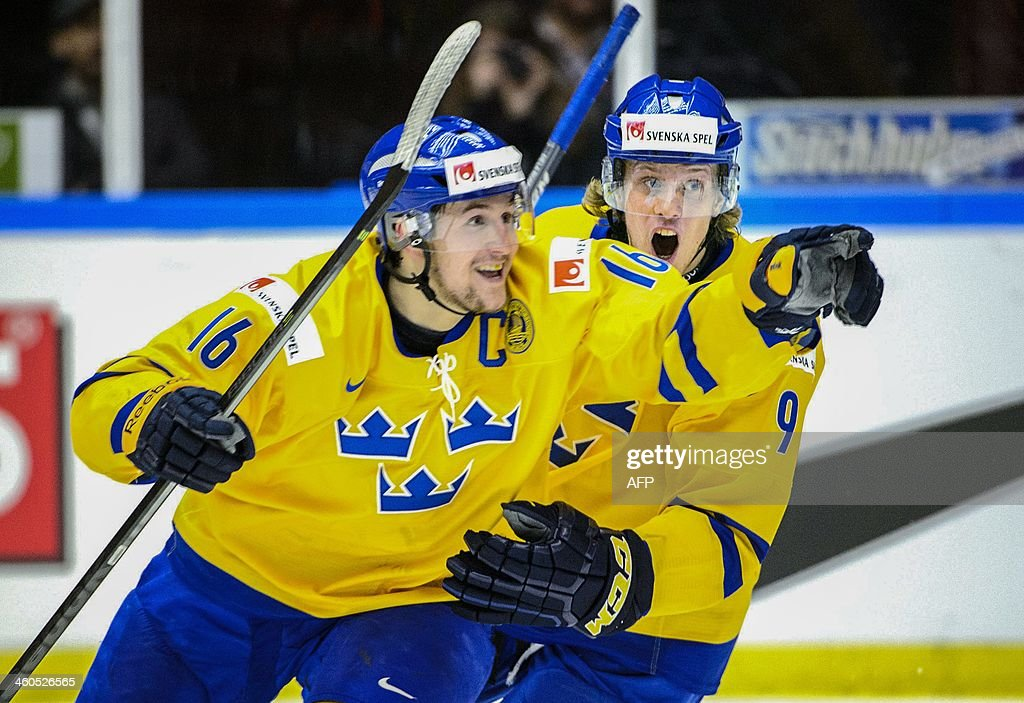 Sweden's Filip Forsberg (L) and his teammate Jacob de la Rose celebrate after scoring during the World Junior Hockey Championships semifinal between Sweden and Russia at Malmo Arena in Malmo, Sweden on January 4, 2014.