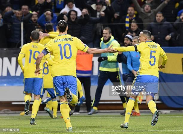 Sweden's forward and team captain Zlatan Ibrahimovic and defender Martin Olsson celebrate after their teammate midfielder Emil Forsberg scored a goal...