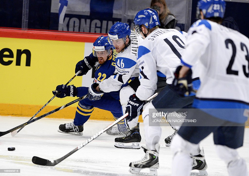 Sweden's forward Daniel Sedin (L) and Finland's defender Janne Jalasvaara (2ndL) vie for the puck during the semi-final match Finland vs Sweden at the 2013 IIHF Ice Hockey World Championships on May 18, 2013 in Stockholm. Sweden won 3-0.