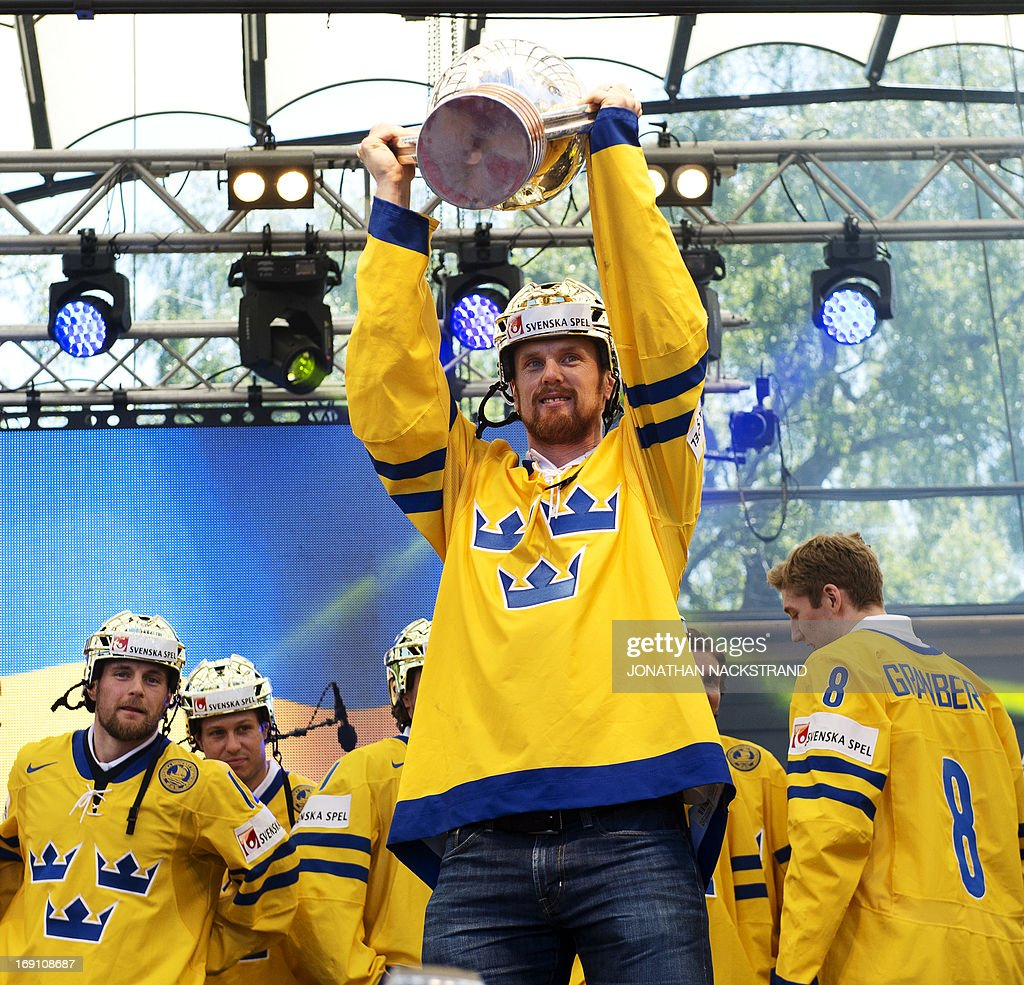 Sweden's forward Daniel Sedin raises the trophy during a victory celebration a day after winning the 2013 IIHF Ice Hockey World Championship, on May 20, 2013 in Stockholm.