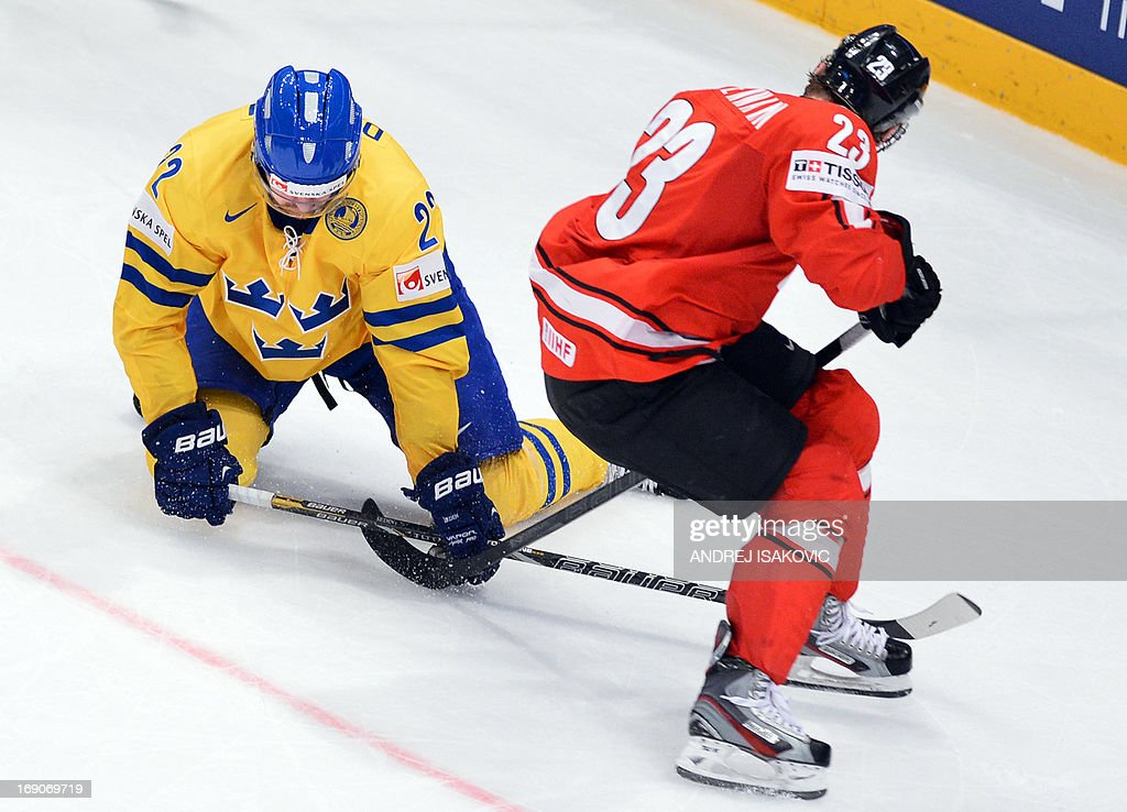 Sweden's forward Daniel Sedin (L) vies with Switzerland's forward Simon Bodenmann during the final match Switzerland vs Sweden of the 2013 IIHF International Ice Hockey World Championship at Globe Arena in Stockholm on May 19, 2013. Sweden won 5-1. AFP PHOTO / ANDREJ ISAKOVIC