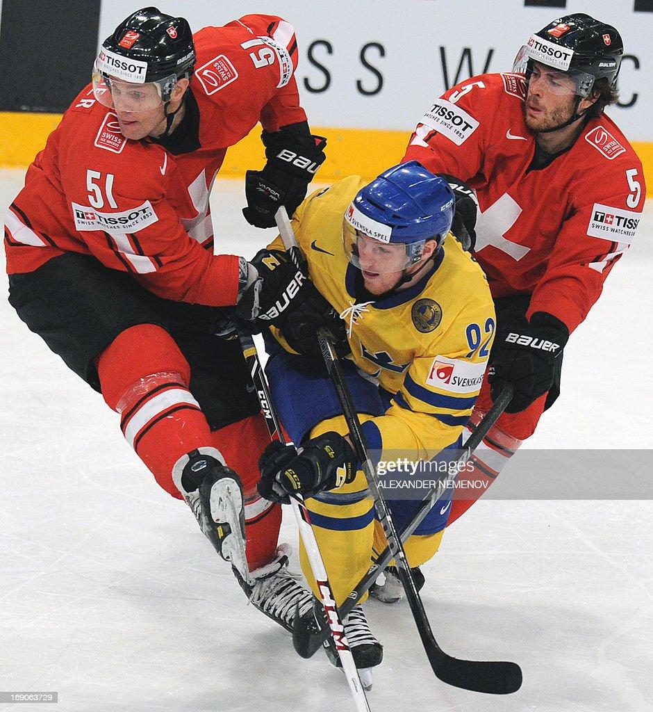Sweden's forward Gabriel Landeskog (C) is sandwiched between Swiss forward Ryan Gardner (L) and Swiss defender Severin Blindenbacher (R) during a final game Switzerland vs Sweden of the IIHF International Ice Hockey World Championship in Stockholm on May 19, 2013. AFP PHOTO/ ALEXANDER NEMENOV RESTRICTED TO EDITORIAL USE