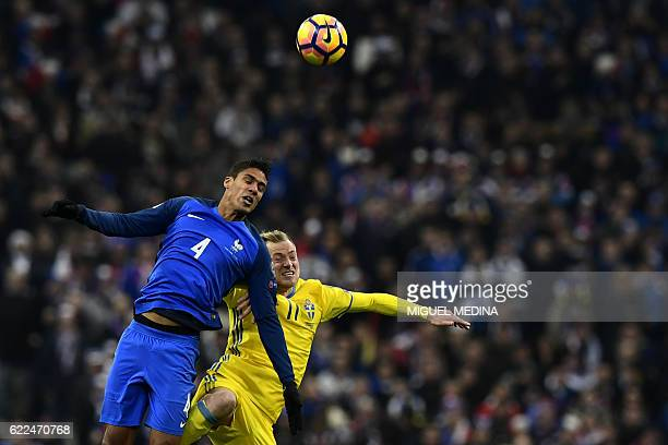 TOPSHOT Sweden's forward John Guidetti heads the ball with France's defender Raphael Varane during the 2018 World Cup group A qualifying football...