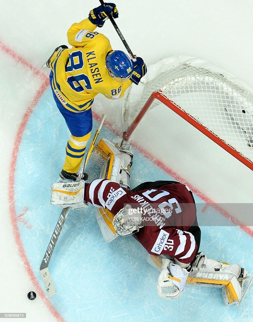 Sweden's forward Linus Klasen (L) vies with Latvia's goalie Elvis Merzlikins during the group A preliminary round game Sweden vs Latvia at the 2016 IIHF Ice Hockey World Championship in Moscow on May 6, 2016. / AFP / Yuri KADOBNOV