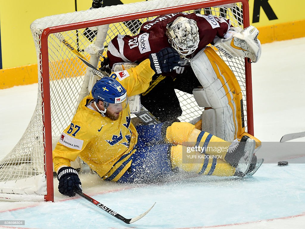 Sweden's forward Linus Omark (L) vies with Latvia's goalie Elvis Merzlikins during the group A preliminary round game Sweden vs Latvia at the 2016 IIHF Ice Hockey World Championship in Moscow on May 6, 2016. / AFP / YURI