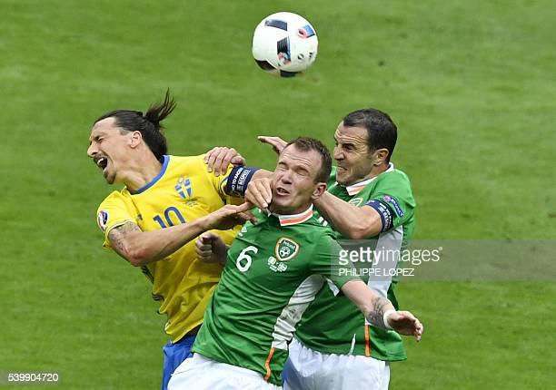 TOPSHOT Sweden's forward Zlatan Ibrahimovic and Ireland's midfielder Glenn Whelan head for the ball during the Euro 2016 group E football match...