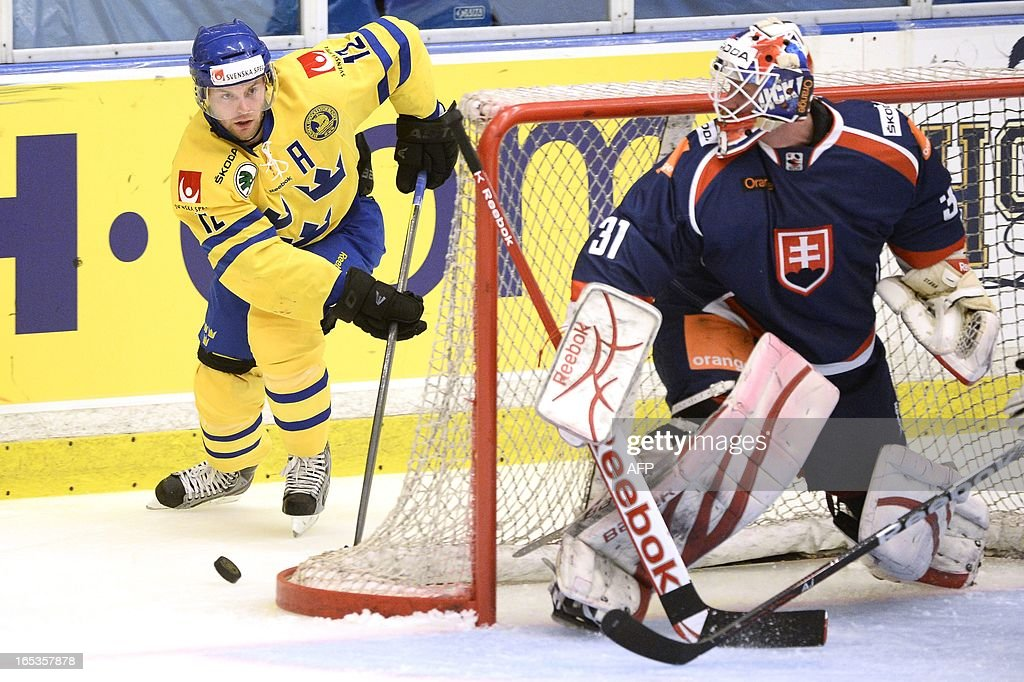Sweden's Fredrik Pettersson (L) is behind the goal mouth of Slovakia's goalie Rastislav Stana during the friendly national icehockey match between Sweden and Slovakia in Oskarshamn, Sweden, on April 3, 2013.