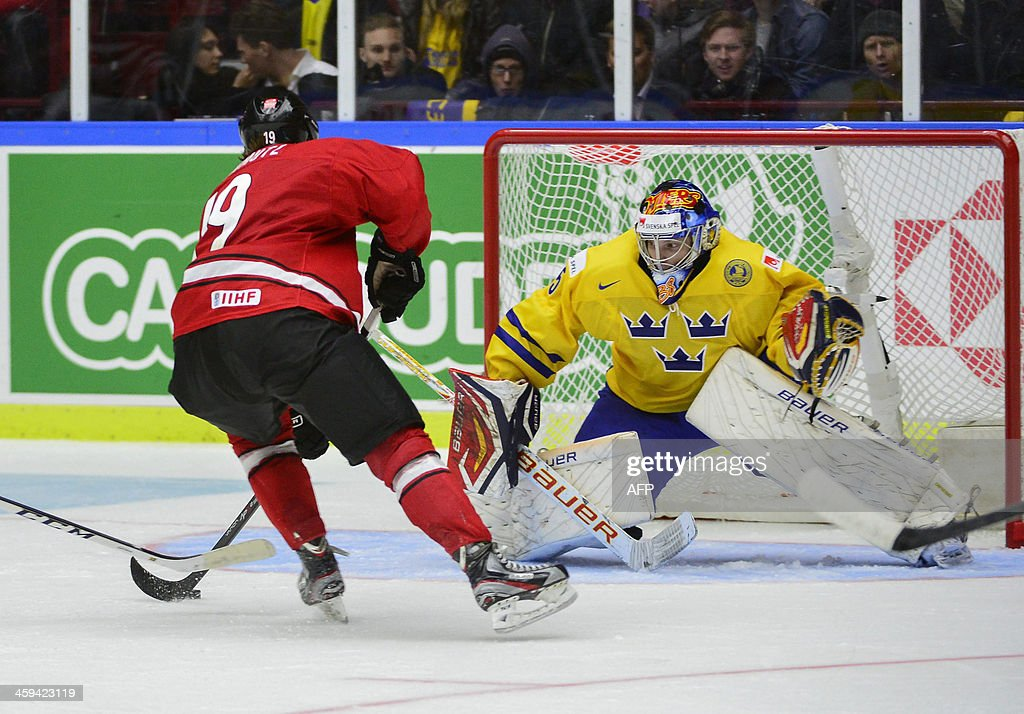 Sweden's goalkeeper Oscar Dansk (R) tries to save a shot from Switzerland's Flavio Schmutz (L) during the Group B preliminary round match Switzerland vs Sweden at the IIHF World Junior Ice Hockey C...