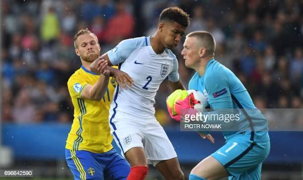 Sweden's Gustav Engvall vies with England's Mason Holgate as England's goalkeeper Jordan Picford grabs the ball during an UEFA U21 European...