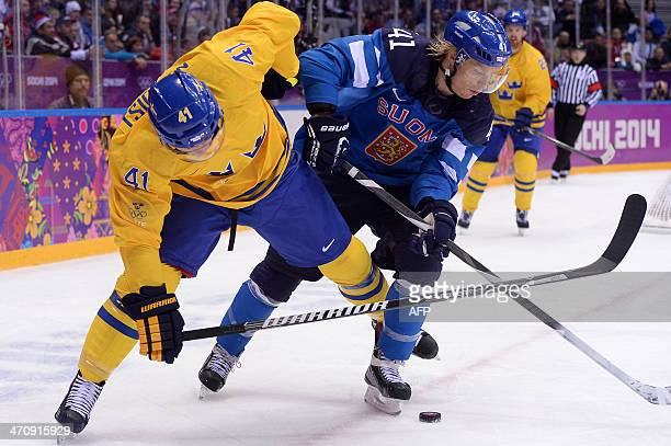 Sweden's Gustav Nyquist vies for the puck with Finland's Antti Pihlstrom during the Men's Ice Hockey Semifinal match between Sweden and Finland at...