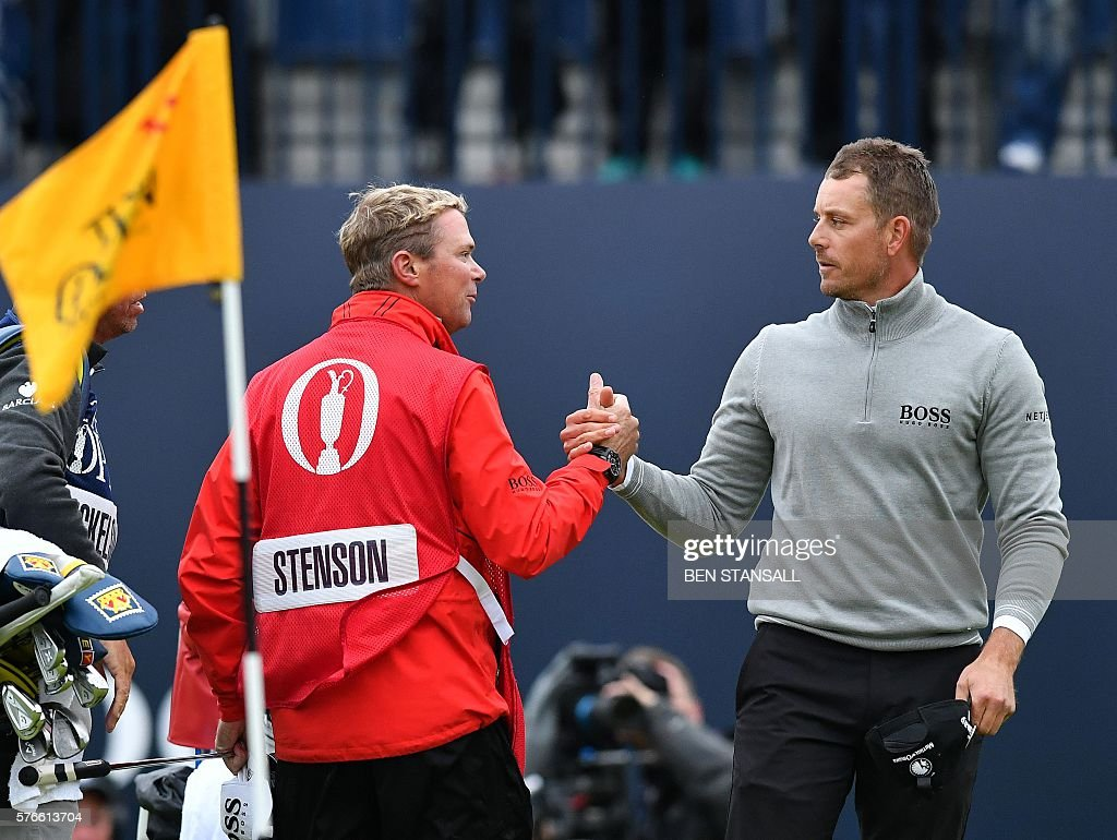 Sweden's Henrik Stenson and his caddie Garath Lord (L) shakes hands on the 18th green after his third round 68 on day three of the 2016 British Open Golf Championship at Royal Troon in Scotland on July 16, 2016. Sweden's Henrik Stenson leads the British Open by a single shot from Phil Mickelson after the third round following his superb 68 on Saturday. Stenson, bidding to win his first major at the age of 40, had five birdies and two bogeys in his three-under-par round to move to 12-under for the championship. / AFP / Ben STANSALL / RESTRICTED