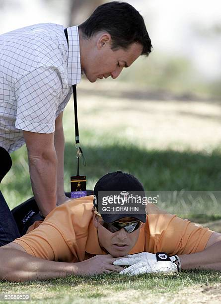 Sweden's Henrik Stenson gets treated by a physiotherapist after he hurt his back during the final round of the 23 million USD Johnnie Walker Classic...
