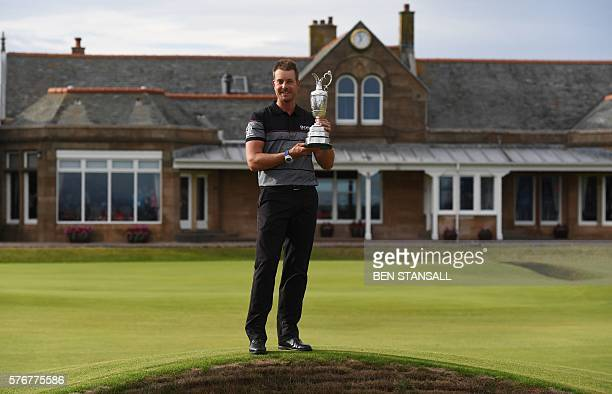 Sweden's Henrik Stenson poses for pictures in front of the clubhouse with the Claret Jug the trophy for the Champion golfer of the year after winning...