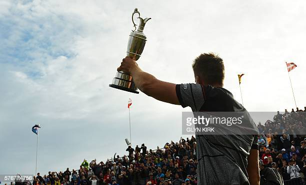 Sweden's Henrik Stenson shows off the Claret Jug the trophy for the Champion golfer of the year to spectators on the 18th hole after winning the 2016...