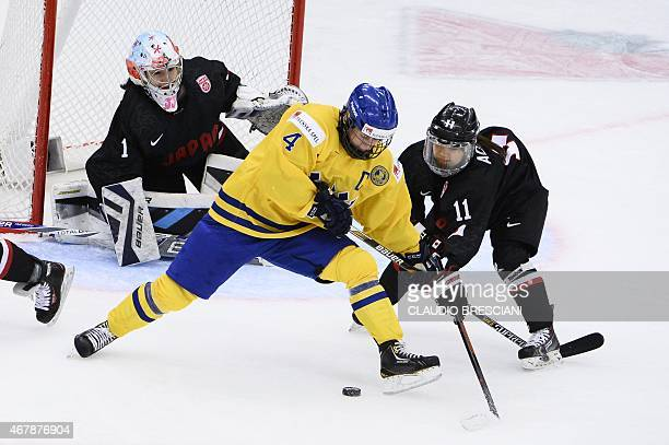 Sweden's Jenni Asserholt vies for the puck with Japan's Yurie Adachi and Japan's goalkeeper Nana Fujimoto during the 2015 IIHF Ice Hockey Women's...