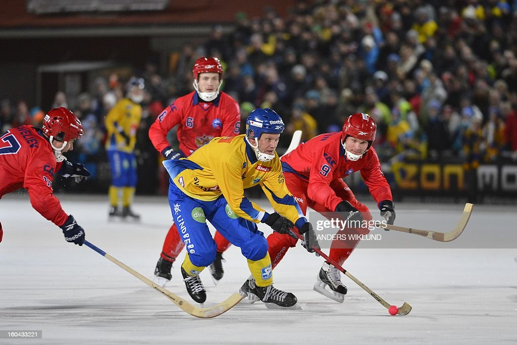 Sweden's Johan Esplund (C) is flanked by Russia's Dmitri Saveliev (L) and Alexander Tyukavin (R) during the Bandy World Championship match between Sweden and Russia in Goteborg, Sweden, on January 31, 2013. AFP PHOTO / ANDERS WIKLUND / SCANPIX SWEDEN / SWEDEN OUT