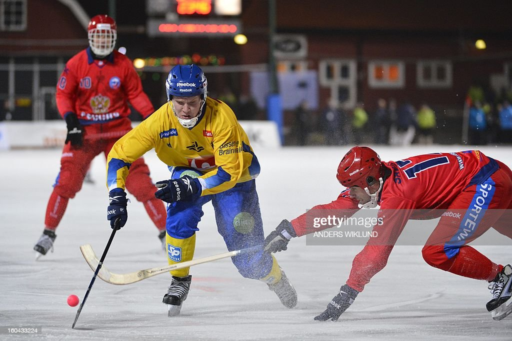 Sweden's Johan Esplund (C) tries to drive the ball past Russia's Dmitri Saveliev (R) during the Bandy World Championship match between Sweden and Russia in Goteborg, Sweden, on January 31, 2013.