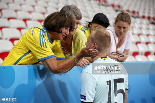 Sweden's John Guidetti is embraced by an unidentified woman in the stands after the final whistle