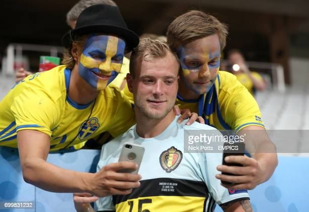 Sweden's John Guidetti poses for a photo with two fans after the game
