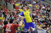 Sweden's Kim Andersson scores a goal against Serbia's Nenad Vuckovic during their 22nd Men's Handball World Championships Main Two group match at the...