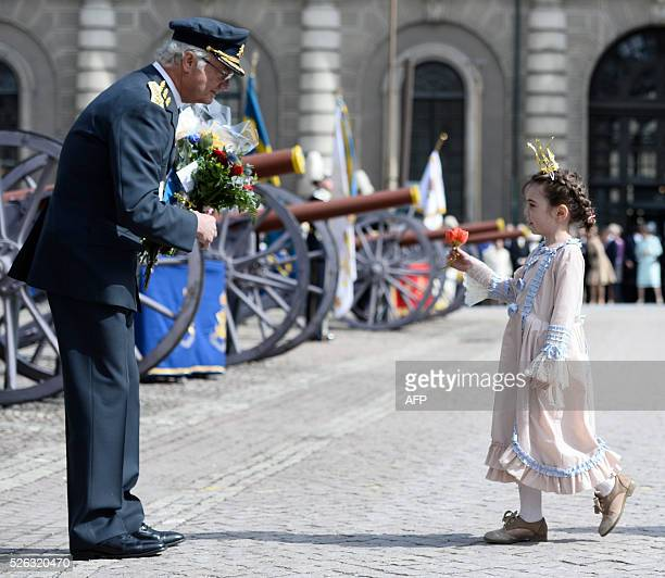 Sweden's King Carl XVI Gustaf is congratulated by a girl dressed as a Princess on the Outer courtyard at the Royal Palace in Stockholm Sweden during...