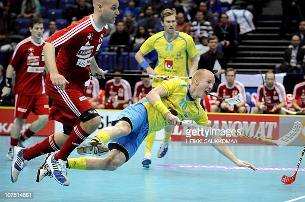 Sweden's Magnus Svensson vies with Switzerland's Simon Bichsel during their Worldcup Floorball Championship 2010 semifinal game in Helsinki on...