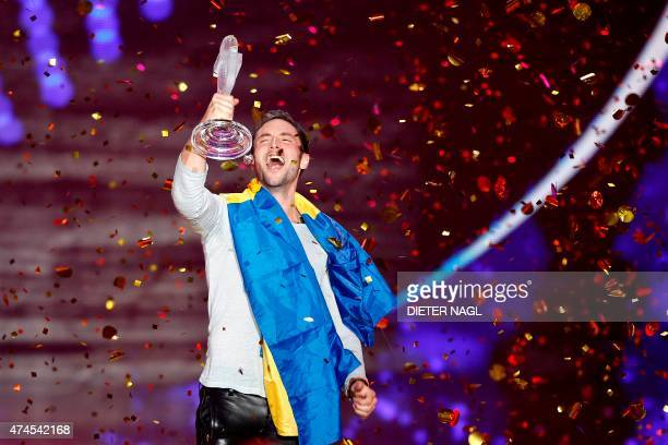 Sweden's Mans Zelmerlow celebrates with the trophy winning the 60th Eurovision Song Contest final on May 23 2015 in Vienna NAGL