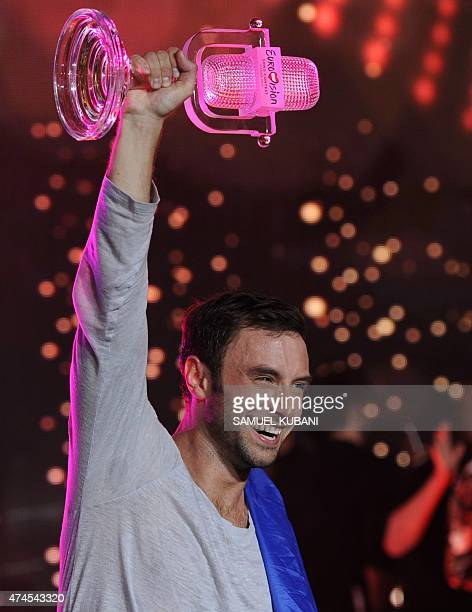 Sweden's Mans Zelmerlow holds the throphy after winning the Eurovision Song Contest final on May 23 2015 in Vienna AFP PHOTO / SAMUEL KUBANI