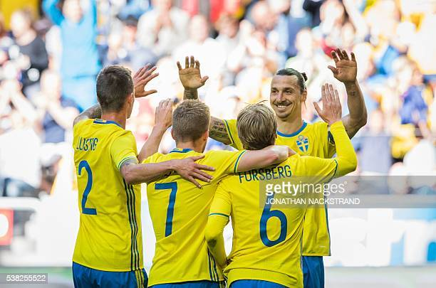 Sweden's midfielder Emil Forsberg celebrates with his forward and team captain Zlatan Ibrahimovic and teammates after scoring a goal during the...