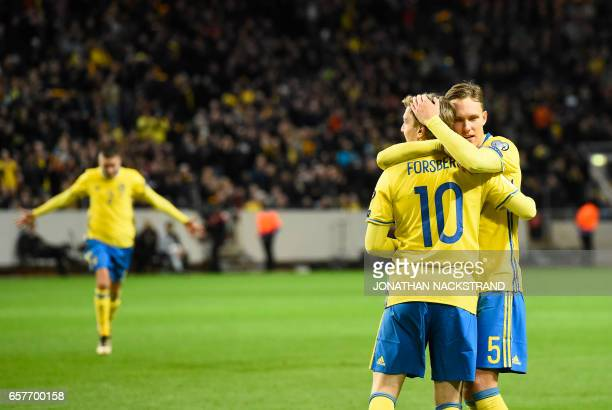 Sweden's midfielder Emil Forsberg celebrates with his teammate defender Ludwig Augustinsson after scoring a goal during the FIFA World Cup 2018...