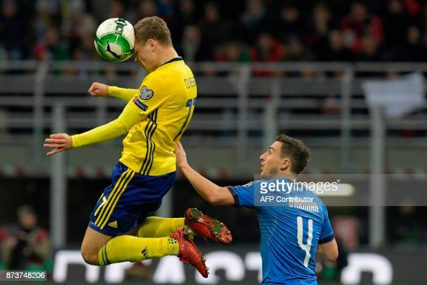Sweden's midfielder Viktor Claesson heads the ball in front of Italy's midfielder Matteo Darmian during the FIFA World Cup 2018 qualification...